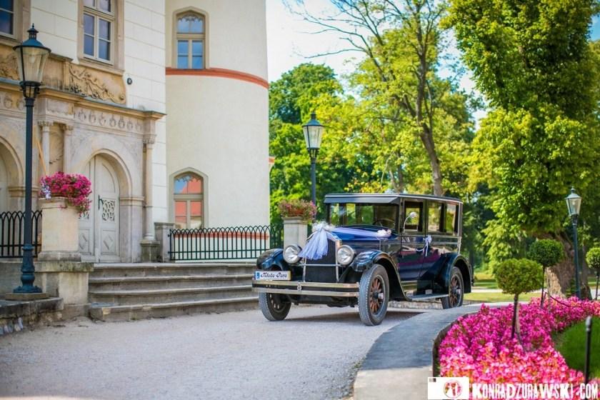 Stylowe auto, którym Państwo Młodzi pojadą do ślubu. A w tle wspaniały budynek Pałacu Wojanów   Fotograf ślubny Konrad Żurawski