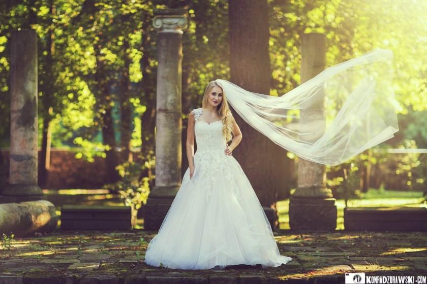 Wiatr we włosach, a raczej w welonie. Ślubne zdjęcie Magdy w przepięknym, pałacowym parku | Fotograf Konrad Żurawski