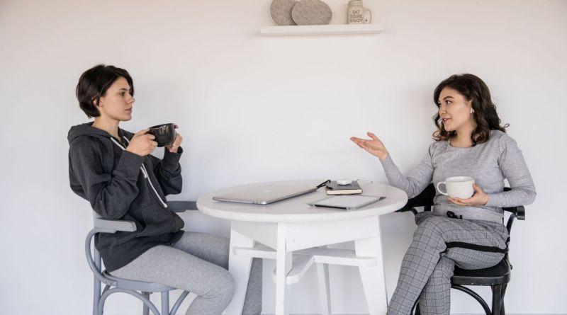 két nő beszélget asztalon könyvek