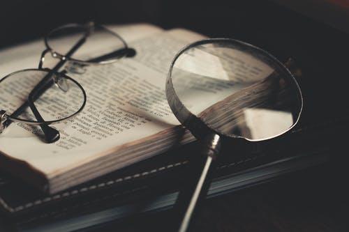 könyv nagyítóval szemüveggel