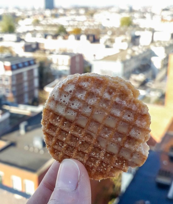 Stroopwafel dipped in a coffee on a rooftop in the Amsterdam city