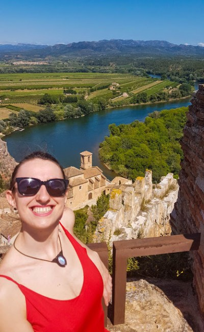 A girl smiling while sitting on the window of Miravet castle overviewing on Ebro river and surrounding area