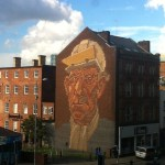 Take12trips: a headshot of a worker painted on the brickwork on the side of a building