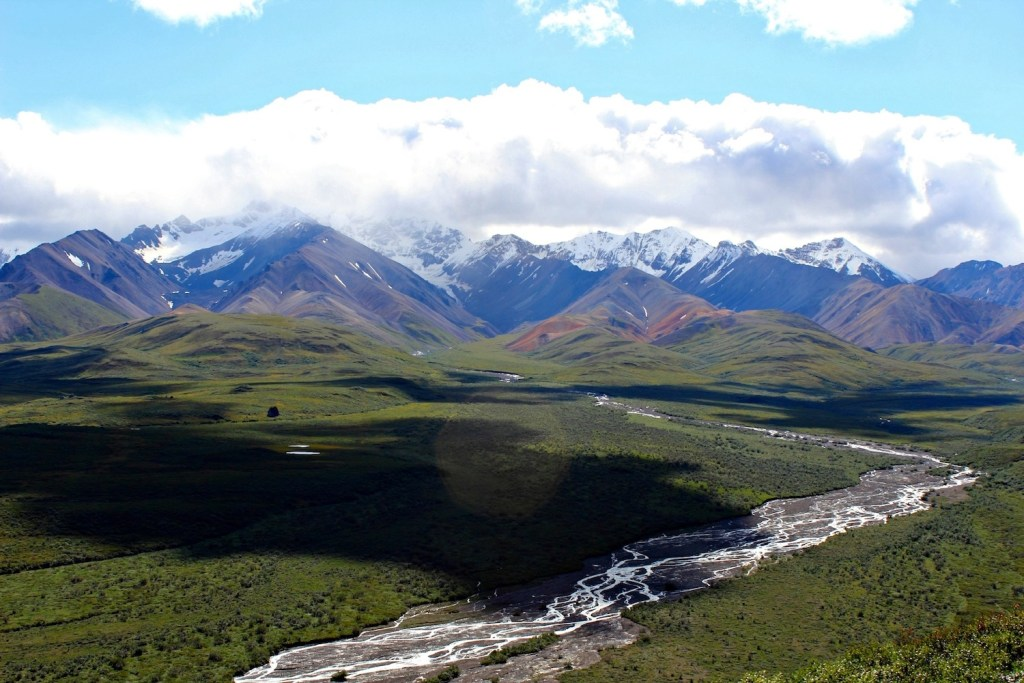 Denali National Park: view of the green tundra and a stream, over-shadowed by a low cloud