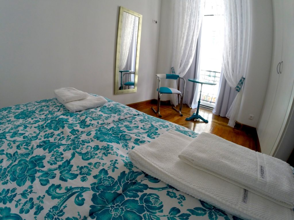 Airbnb Lisbon: master bedroom - bed faces a balcony with a chair and table in the window