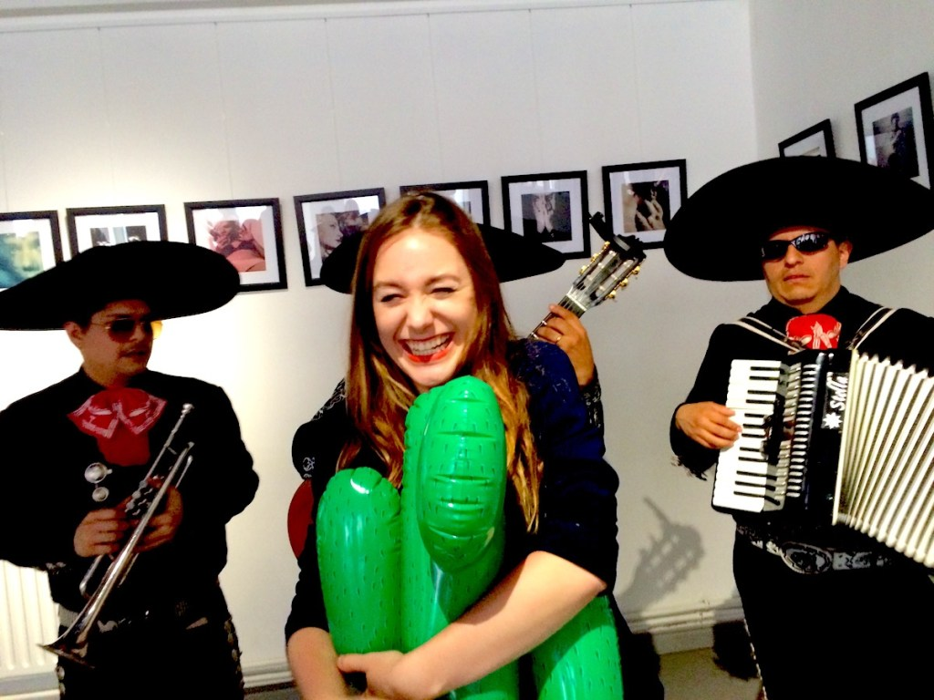 Sabina from Girl vs Globe hugging a cactus in front of the mariachi band