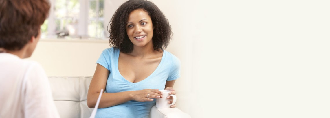 Woman talking with medical professional and drinking coffee