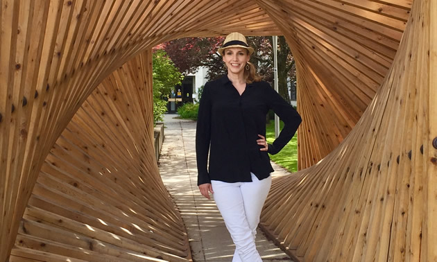 "Joy Barrett, cultural development officer for Nelson, B.C., and executive director of Castlegar Sculpturewalk, stands within ""Sculpture Walk"" by Spring Shine, Christopher Petersen and Hans Winter (2016)."