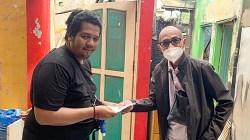 Pengacara Supiansyah Darham (kanan) menyerahkan bantuan kepada wartawan, Wahyu (kiri).