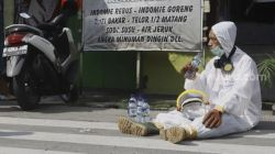Petugas Palang Merah Indonesia (PMI) beristirahat di sela-sela menyemprotkan cairan disinfektan di lingkungan asrama Sekolah Tinggi Teknologi (STT) Bethel di kawasan Petamburan, Jakarta, Jumat (17/4). [Suara.com/Angga Budhiyanto]