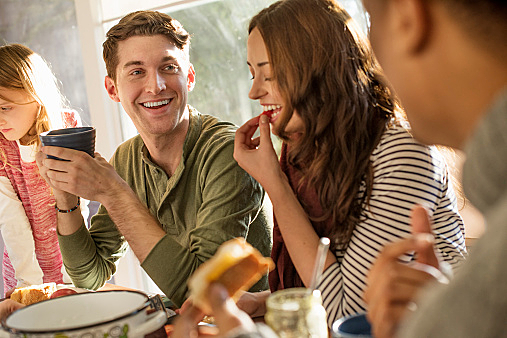 A group of people sitting at a table, smiling, eating, drinking and chatting.