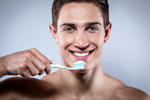 Young smiling man with toothbrush