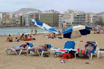 Tourists sleep on the beach of Las Palmas on island of Gran Canaria, Canary Islands, Spain.