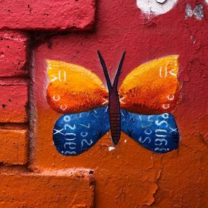 Orange and blue butterfly painted onto a wall mural