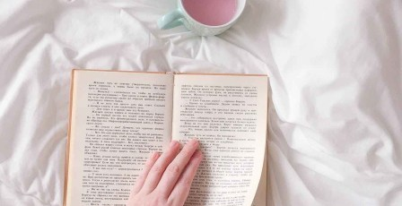 person holding book on white surface