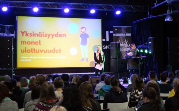 Yhdessä ei olla yksin -hankkeen projektipäällikkö Sirpa Pekkarinen pitämässä puhetta täydelle salille Veturitalleilla. Lavalla myös projektikehittäjä Anja Saksola.