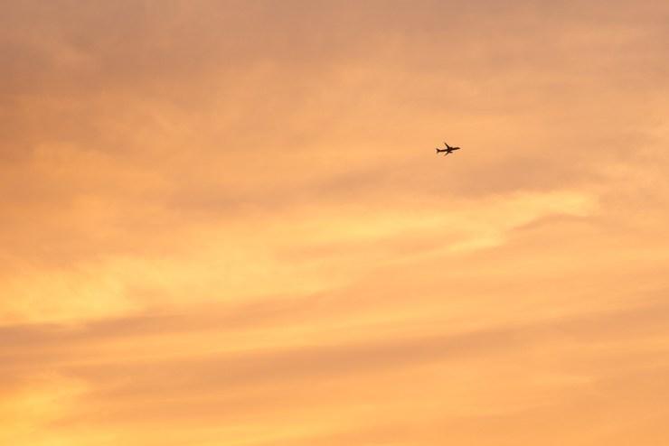 夕焼けの中を飛ぶ飛行機