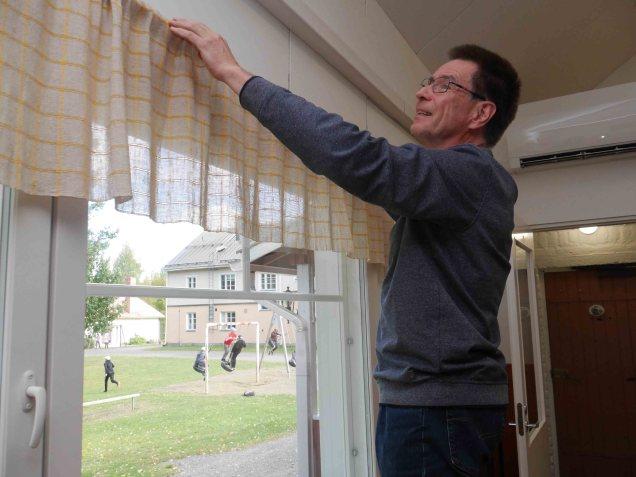 Pekka Ranne asentaa uusittujen ikkunoiden verhotankoja paikoilleen.