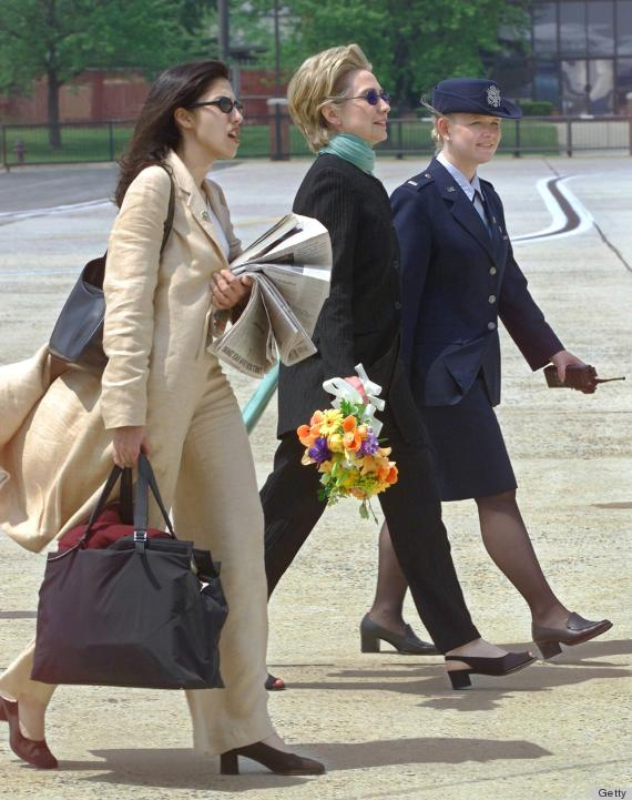 ANDREWS AIR FORCE BASE, UNITED STATES: US First Lady and New York Senate candidate Hillary Clinton(C) carries flowers and is led by an unidentified Andrews Air Force Base Protocol Officer(R) while her personal aide Huma Abedin carries a bag and a stack of New York newspapers 06 May 2000 after returning from New York to meet up with her husband, President Bill Clinton at Andrews Air Force Base, Maryland. The Clintons then boarded Air Force One and traveled to Subiaco, Arkansas, to attend a friend's wedding . (ELECTRONIC IMAGE) AFP PHOTO PAUL J. RICHARDS (Photo credit should read PAUL J. RICHARDS/AFP/Getty Images)