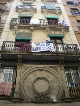 "The banner of this apartment building in Raval says in Catalan ""We want a decent neighborhood"". Raval area, one of the most historic in Barcelona, used to be well-known as the city's red-light district. It is also a very multicultural place crowded with people from Asian, African and Latin American countries."