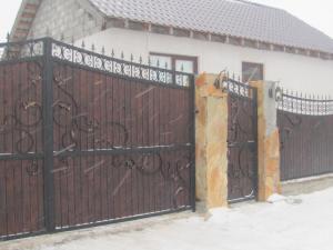 Кованые ворота с досками из лиственницы.