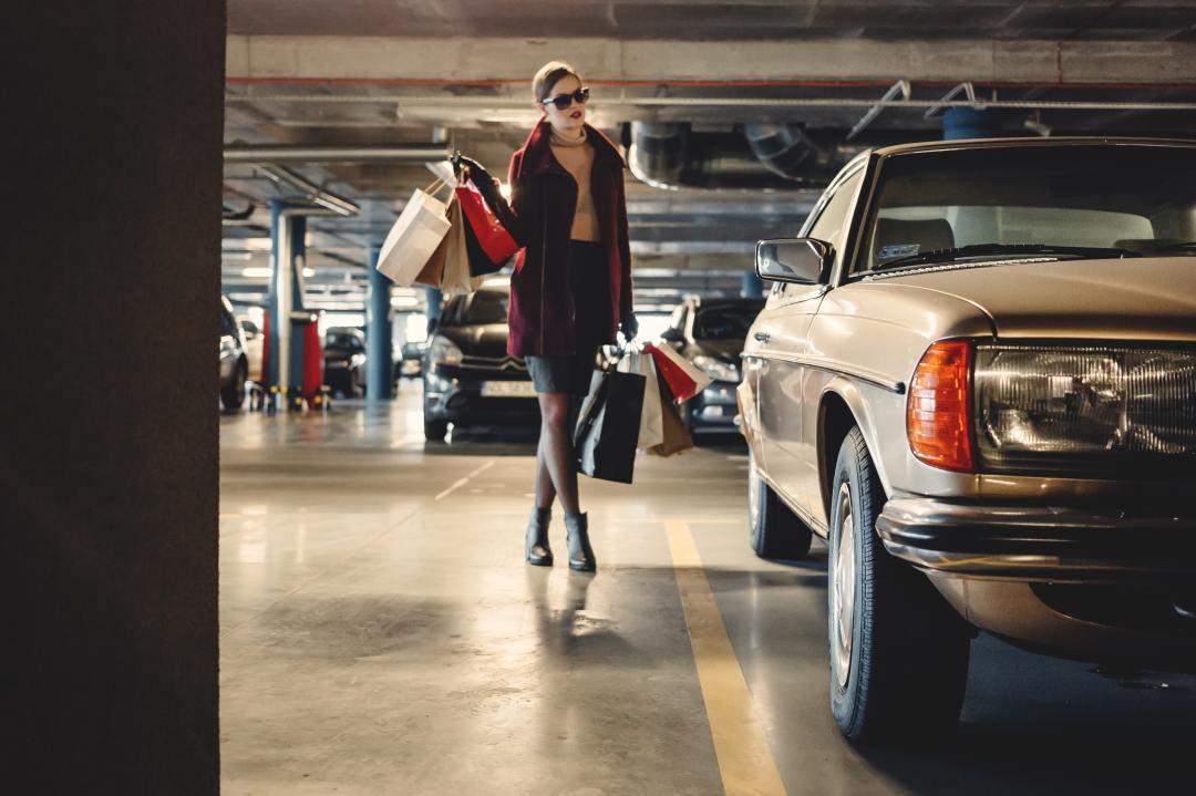 Femme dans un parking avec des sacs à côté d'une voiture