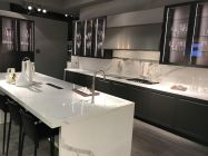 Black-and-white-kitchen-layout-with-glass-cabinet-doors-and-waterfall-countertop