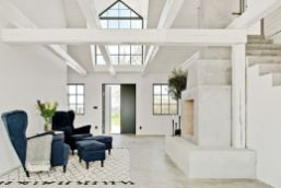 Fireplace-with-accent-chairs-on-front-Barn-Coversion-in-Sweden