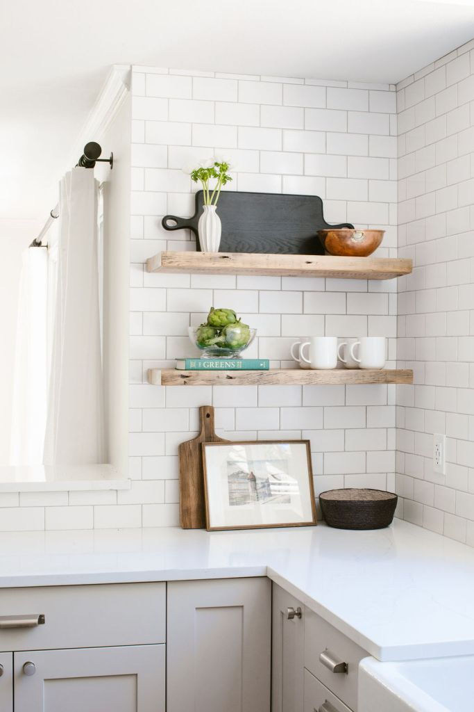 Open shelving in a modern-rustic kitchen with vintage frame, bowls and decor.