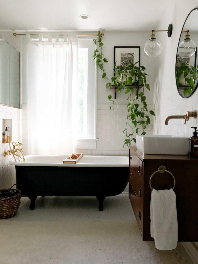 A vintage bathtub and bathroom vanity in a bright, white bathroom.
