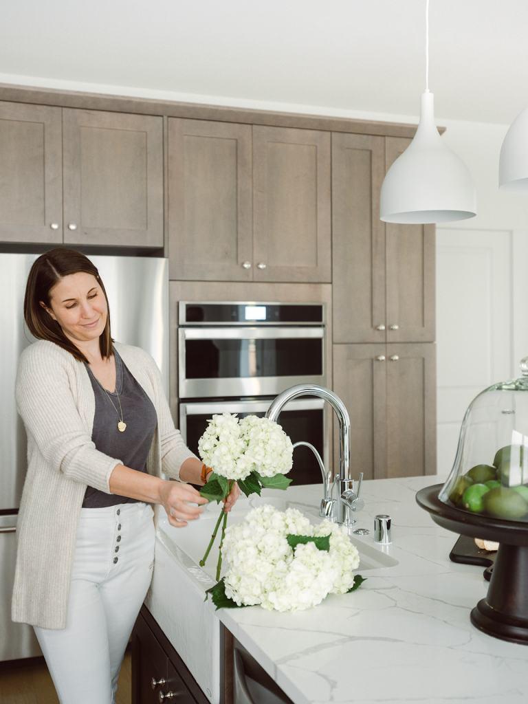 Krissy arranging flowers in kitchen