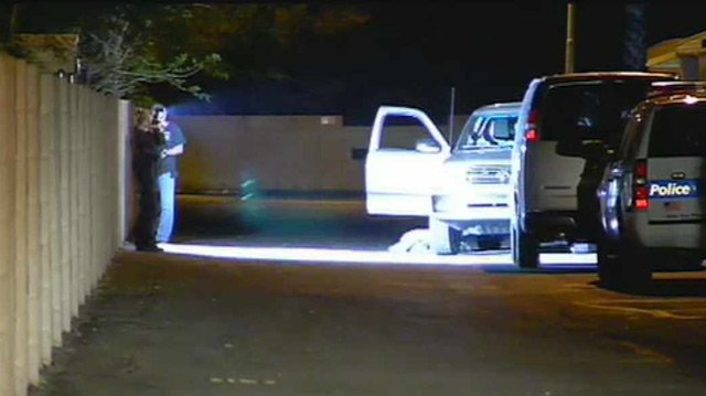 Investigators photograph a stolen pickup truck, in which a man was found handcuffed and with a bag over his head Monday night. (Source: CBS 5 News)