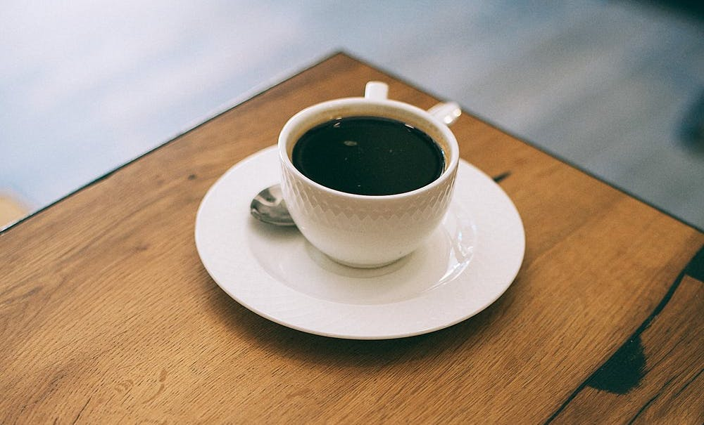 organic black coffee in a white cup sitting on a table