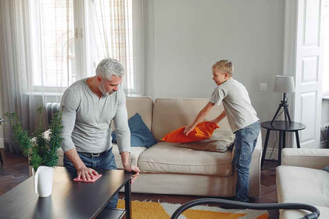 father and son spring cleaning in the living room