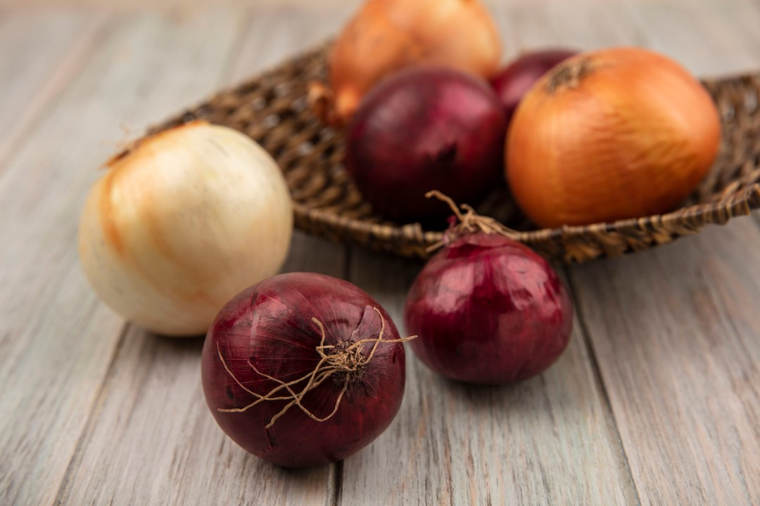 top view of red and white onions on a wicker tray on a grey wooden background