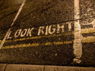 """Crosswalk with """"Look Right"""" painted at the transition to the street."""