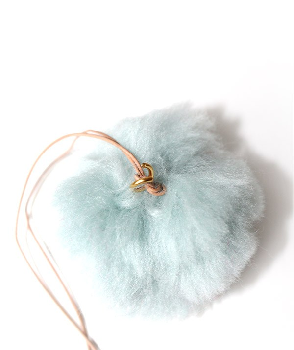Make a knot at the end of the pom and attach one jump ring.