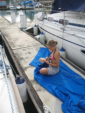 Janička přešívá krycí plachty.