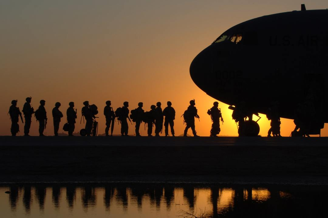 Soldiers on queue ready to board an airplane with a glistening sunset in the horizon