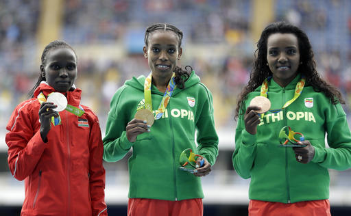 Winner Ethiopia's Almaz Ayana, center, second placed Kenya's Vivian Cheruiyot, left, and third placed Ethiopia's Tirunesh Dibaba stand on the podium after the women's 10,000-meter final during the athletics competitions of the 2016 Summer Olympics at the Olympic stadium in Rio de Janeiro, Brazil, Friday, Aug. 12, 2016. (AP Photo/David Goldman)