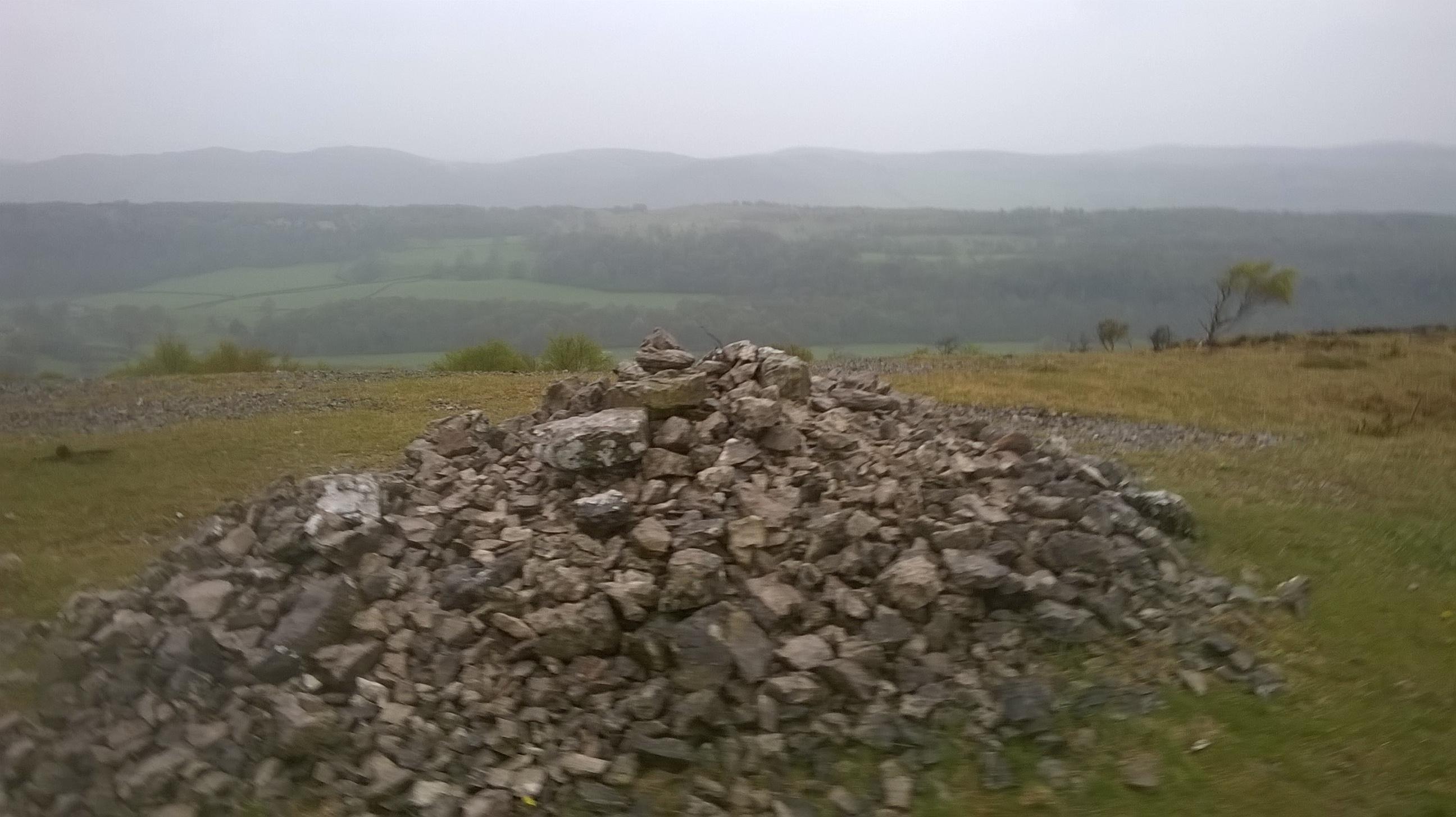 Kalna virsotnē sakrauta akmeņu kaudze un skats uz visām pusēm