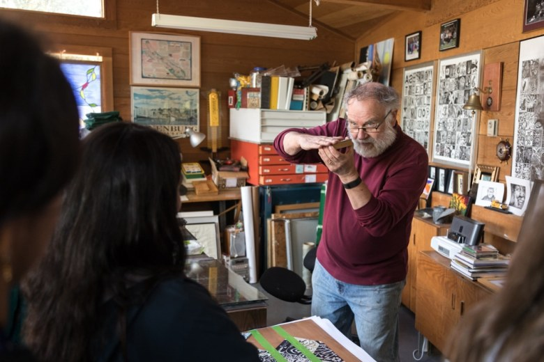 Peter Scurr trains high-school art students on how to ink and operate the old printmaking press