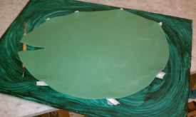 Fondant covered cake board and green fondant lily pad. The bits of waxed paper give the lilly pad an added dimension when dry.