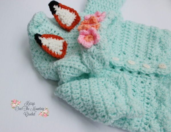 Your little one will look so sweet in this crocheted Baby Fox sweater. The hood has a crown of flowers, fox ears and a box pleat at the point of the hood. Such a sweet design.