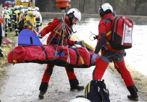 Rescue teams salvage an injured person at the site of a train accident near Bad Aibling, Germany, Tuesday, Feb. 9, 2016. Several people were killed when two trains collided head-on. (Uwe Lein/dpa via AP)