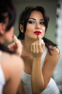 Woman doing make-up, beautiful young woman doing make-up and smiling while looking at the mirror