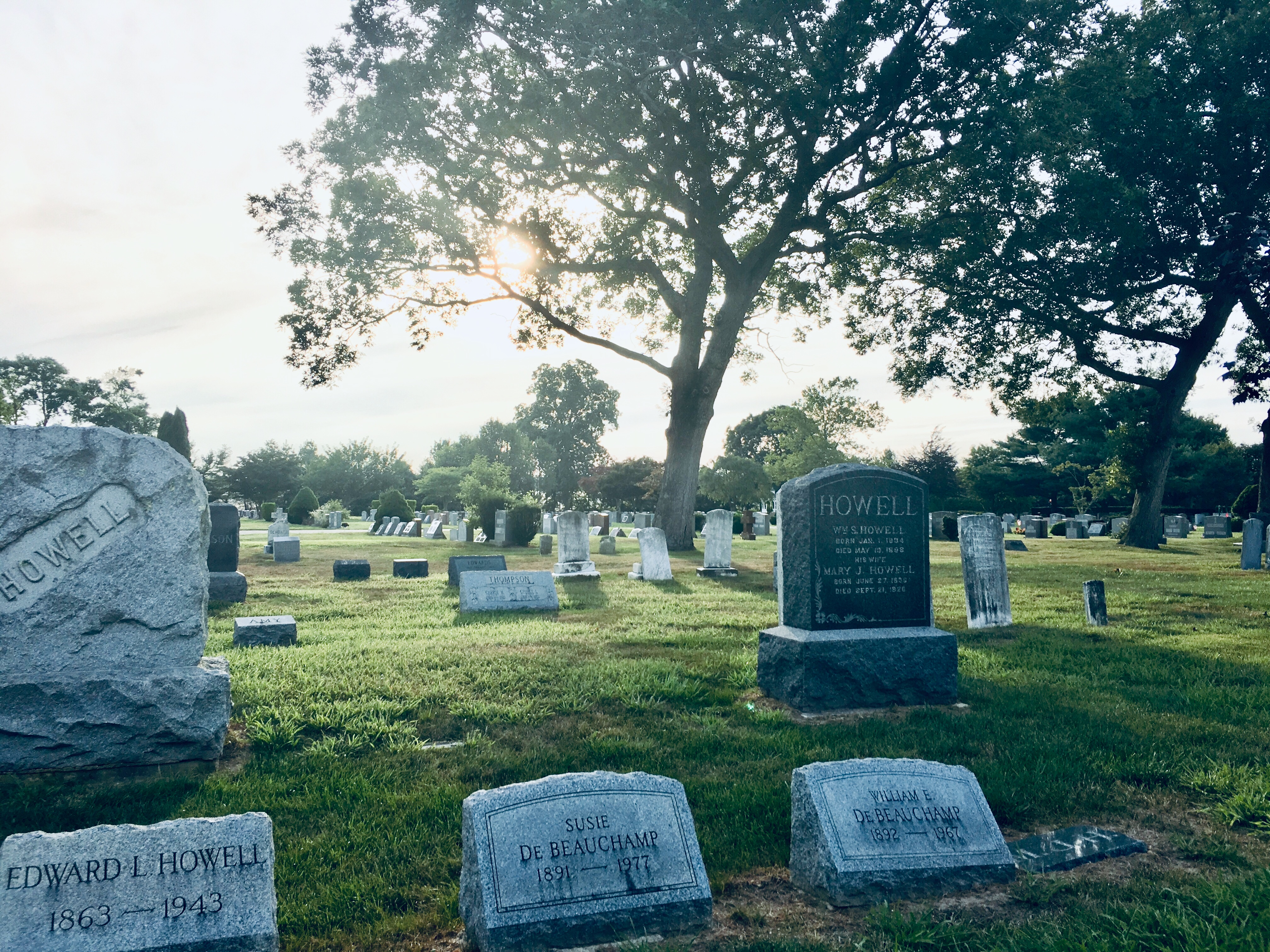 """A photo of a cemetery. In the foreground are three headstones reading """"Howell"""" and two reading """"De Beauchamp."""" Two tall trees stand in the background, blocking the light of a setting sun."""