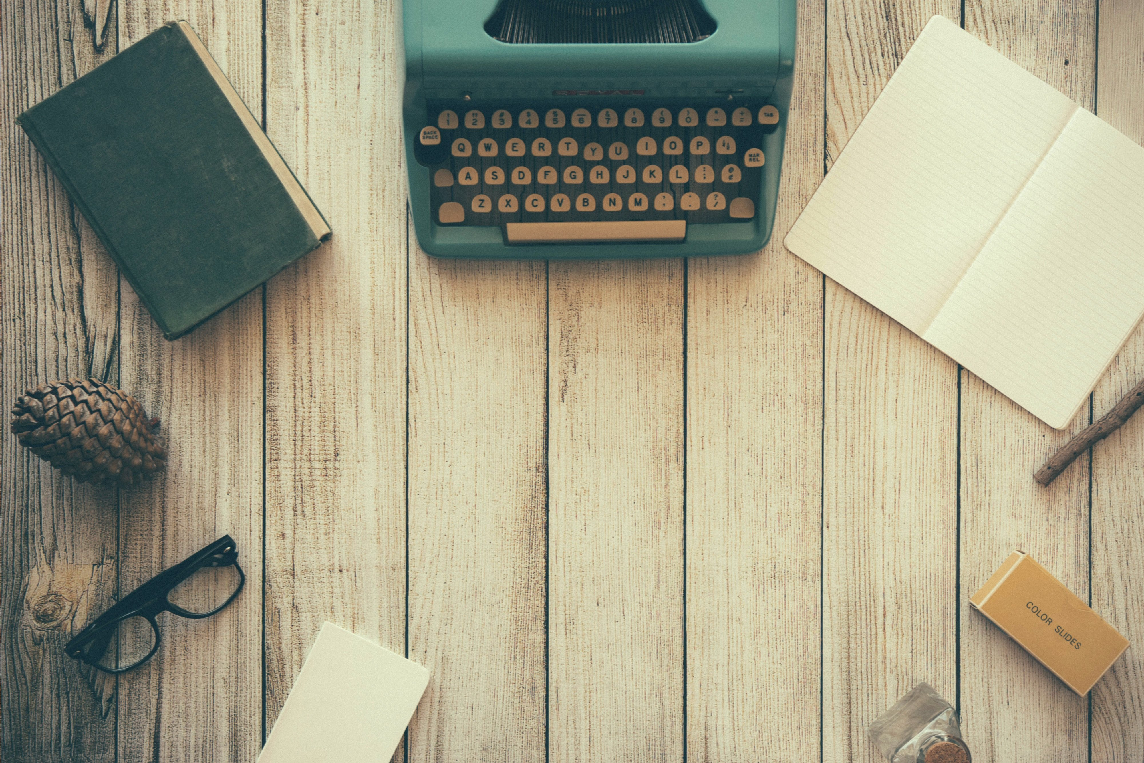 An image of a wooden tabletop from above. On the table lay a blue typewriter, an open empty notebook, a box of film slides, a pair of glasses, an old book, and a pinecone.