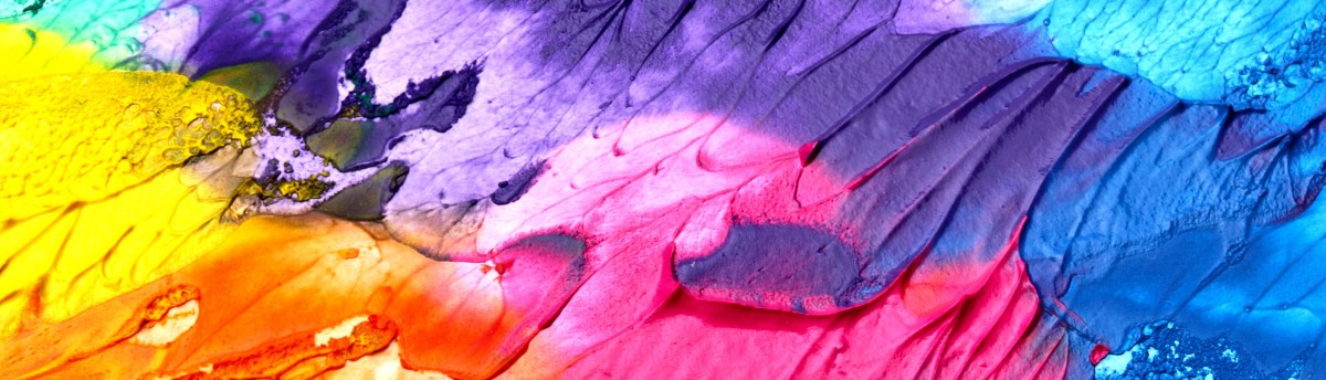A close-up of a canvas besmeared with rainbow colored paint, which blends into each other.