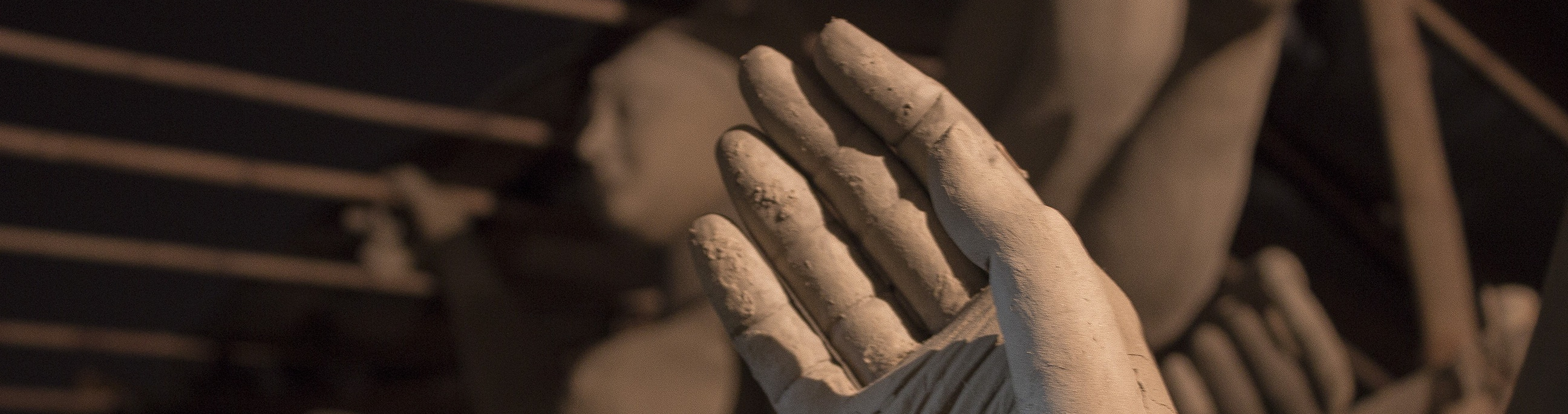 A close-up of a clay human hand. Behind the hand are a multitude of clay bodies.